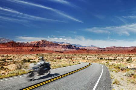 Motorcycle traveler riding in American highway, Glen Canyon, Utah, USA. Main object in motion blur