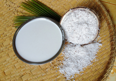 coconut milk with coconut flakes and leaves isolated on winnowing rice. copy space