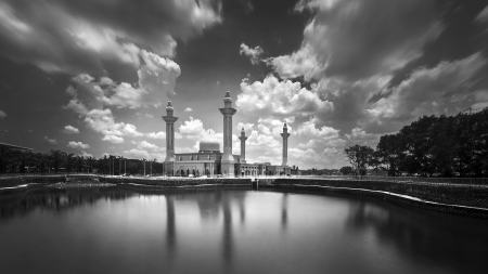 Mosque and moving clouds with reflection on the lake in black and white photo