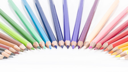 colored pencils arranged in a curved  isolated white background photo
