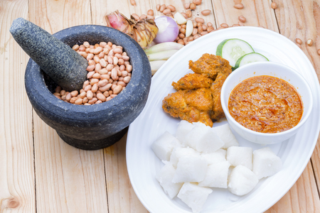 Chicken Rendang is popular dishes in Malaysia, with onion, peanut and lemongrass as decoration on wooden table
