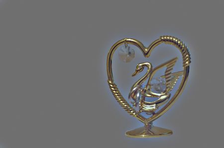 Golden swan carrying two wedding rings