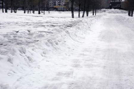 Snow-covered path in the town park