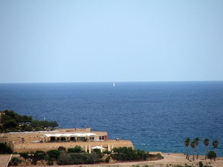 View on littoral hotal and far sail that is visible at sea