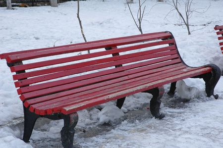 Old bench made from massive cast-iron legs and wooden boards colored red paint Stock Photo