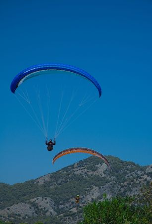 Photo of two paragliders landing after long fly over coast of the Mediterranean sea Stock Photo