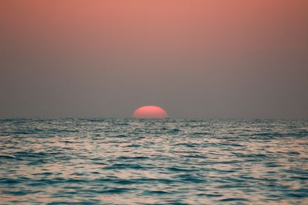 Photo of red sun sets beyond the Mediterranean sea