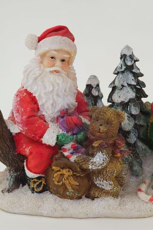 Photo of toy Santa Claus and bear holding a rucksack with toys and gifts