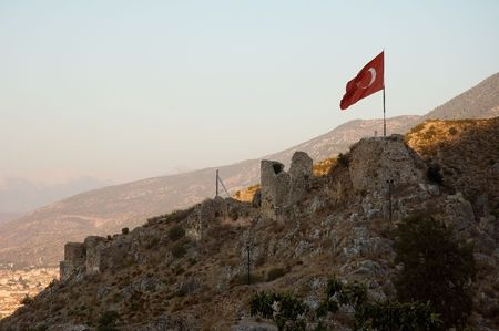 Turkish flag flattering on the ancient castle ruins near Fethye