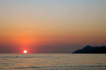View from a beach red sunset over the Mediterranean sea photo