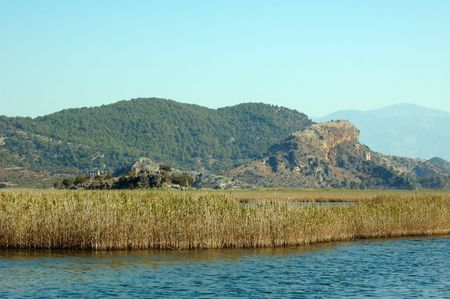 rushy: Rushy river coast with mountains and sky on background