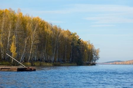 Autumn landscape with yellow forest at the coast of lake Stock Photo