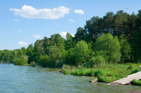 Photo of lake coast with green trees and wooden footbridge