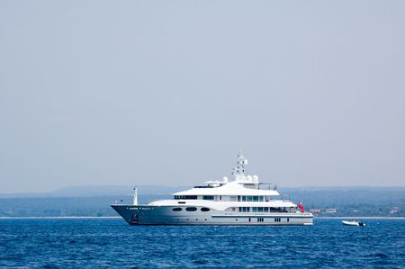 View on a majestic yacht ploughs water of the Mediterranean sea