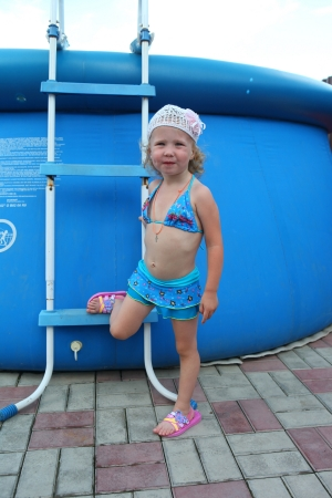 A little girl in a bathing suit in a large inflatable pool photo