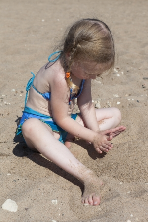 Girl playing with sand on the beach photo