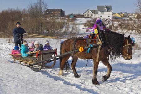 horse sleigh: Children ride in a sleigh horse Shrovetide  Verkhovazhye village, Vologda region, Russia Editorial