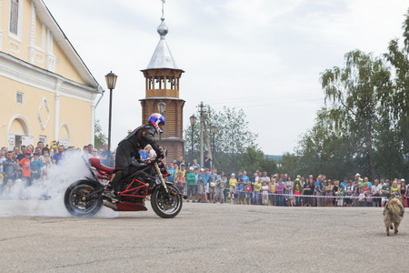 Motorcycle Show on Cathedral Square in village Verkhovazhye, Vologda Region, Russia  Alexei Kalinin burneth his motorcycle tires Editorial