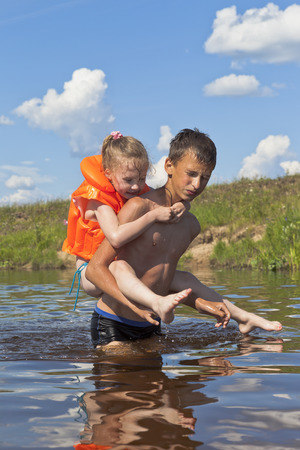 helps: Serious boy carries a cheerful little girl across the river Stock Photo