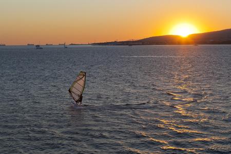 krasnodar region: Windsurfer against the setting sun in Gelendzhik Bay. Gelendzhik, Krasnodar region, Russia Stock Photo