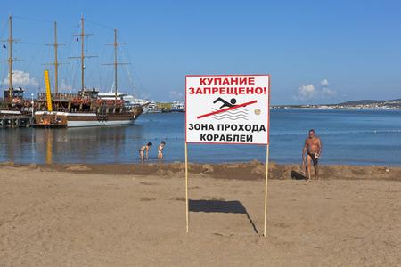 """personas banandose: El signo """"No nadar! Pasaje Zona de buques"""" en el fondo de las personas que se ba�an en el muelle en Gelendzhik, regi�n de Krasnodar, Rusia Editorial"""