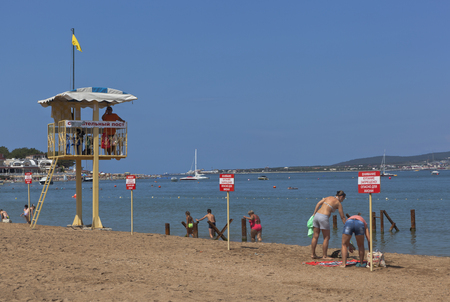 no swimming: Vacationers people ignore the warning signs that says Warning! No swimming! Danger to life. Beach resort city Gelendzhik, Krasnodar Krai, Russia
