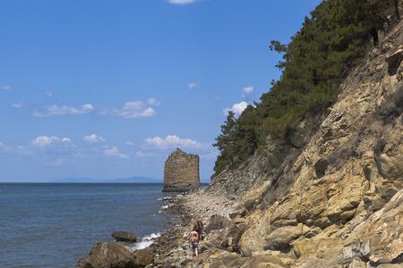 krasnodar region: Tourists walk along the rocky shore of Black sea to the monument of nature Sail Rock. Gelendzhik, Krasnodar region, Russia Stock Photo