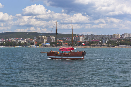 krasnodar region: The yacht Pharaoh floats in Gelendzhik Bay on the background of Central Beach resort of Gelendzhik