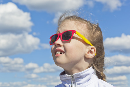 Dreamy small girl wear sunglasses against the sky with clouds looking at the top