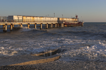 granola: Big wave covered breakwater at the pier in the resort settlement of Adler in the setting sun, Sochi, Krasnodar region, Russia