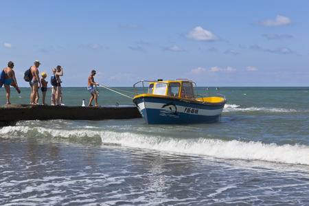 Cather is moored off to a concrete breakwater for boarding of passengers from the beach resort of settlement Adler, Sochi, Krasnodar region, Russia Editorial