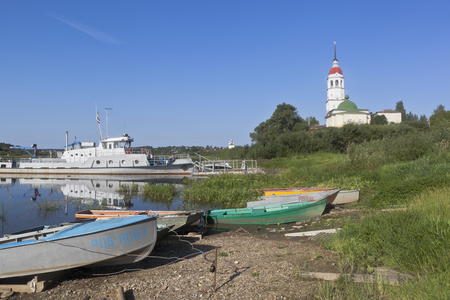 Boat parking at the shore Sukhona river near the church Assumption of the Blessed Virgin in the town of Totma, Vologda Region, Russia