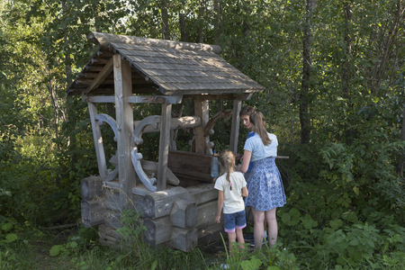 gaining: Children are gaining spring water from a spring in the form of the well