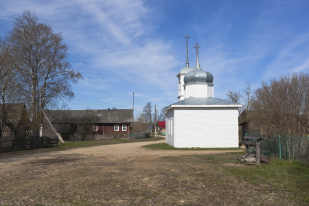 street creed: Landscape streets of the northern village in the spring. Chapel of the Assumption of the Blessed Virgin Mary in the village of Mokievskaya, Verkhovazhsky district, Vologda region, Russia
