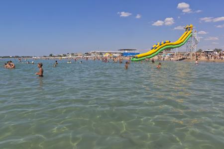 Children bathe in the clear water of the Black Sea at the beach Rodnichok in the resort town of Evpatoria, Crimea, Russia