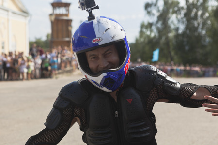 Alexei Kalinin is a motorcycle show in the village Verkhovazhye and welcomes the audience by the hand in the circles in Verkhovazhye, Vologda region, Russia