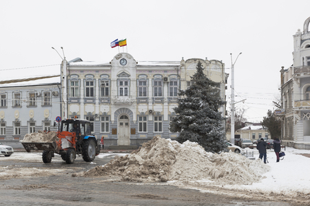 Evpatoria, Crimea, Russia - February 28, 2018: Snow-removal work on the background of the building of the administration of Evpatoria, Crimea