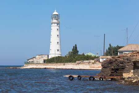 Wooden pier for excursion boats against the background of the Tarkhankut lighthouse, Crimea, Russia