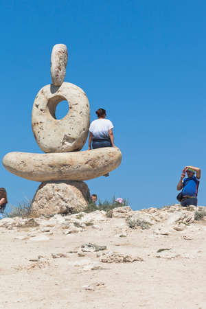 Chernomorsky District, Crimea, Russia - July 21, 2020: Tourists are photographed near the Thinker sculpture on the White Rock of Cape Tarkhankut, Crimea Editorial
