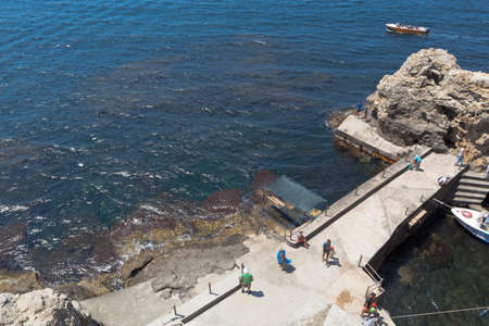 Chernomorsky District, Crimea, Russia - July 21, 2020: Concrete pier with tourists at the Bolshoi Atlesh Cape of the Tarkhankut Peninsula, Crimea Editorial