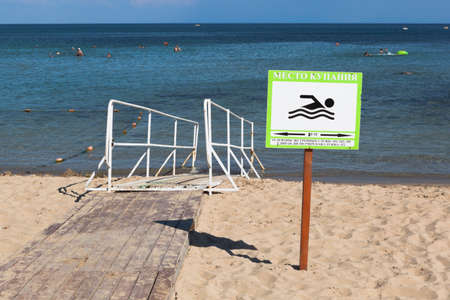 Zaozyornoye, Evpatoria, Crimea, Russia - July 22, 2020: A sign of a bathing place against the background of a ramp for entering the sea of disabled people on the Barabulka beach in the village of Zaozyornoye, Evpatoria, Crimea