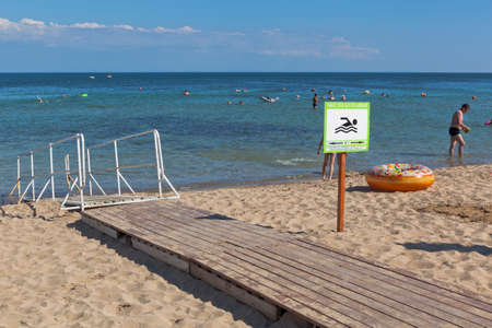 Zaozyornoye, Evpatoria, Crimea, Russia - July 22, 2020: A ramp for entering the sea of disabled people on the Barabulka beach in the resort village of Zaozyornoye, Evpatoria, Crimea