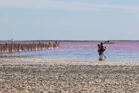 Evpatoria, Crimea, Russia - July 23, 2020: Tourists on the pink lake Sasyk-Sivash near the city of Evpatoria, Crimea