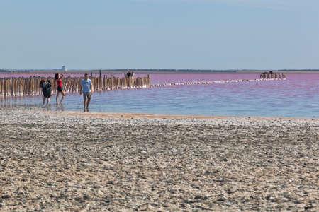 Evpatoria, Crimea, Russia - July 23, 2020: Tourists on the shore of the pink lake Sasyk-Sivash near the city of Evpatoria, Crimea Editorial