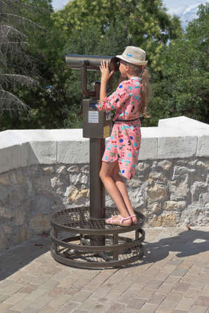 Sevastopol, Crimea, Russia - July 27, 2020: Girl looks in the binoculars fixed on the viewing platform of the memorial complex Malakoff in the city of Sevastopol, Crimea