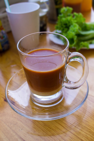 res: a cup of thai tea on table made from dimsum restaurant,blur background