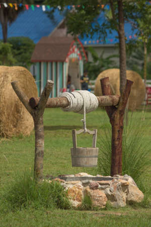 groundwater: water well, rope and wooden bucket  Stock Photo