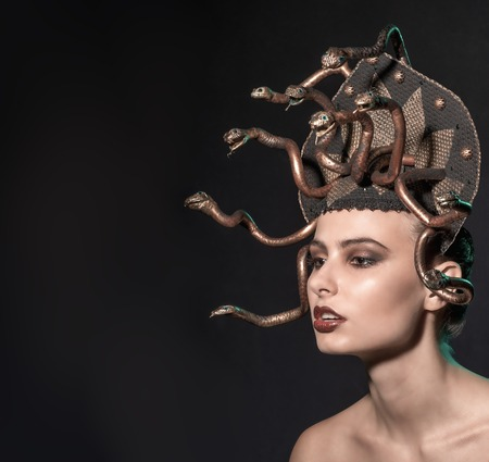 ancient sexy: girl Medusa headdress of gold color on a black background.