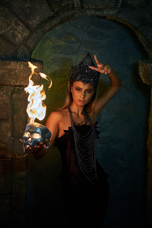 girl in gothic costume holds a burning skull in darkness