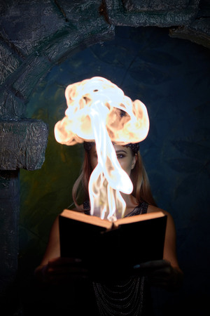 girl in a gothic suit holds a burning book 写真素材